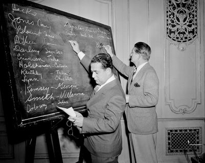 """In this April 18, 1943, file photo, Fred Mandel, foreground, president of the Detroit Lions, and Charles """"Chile"""" Walsh, assistant coach of the Cleveland Rams, look over prospects at the player draft of the NFL in Chicago. The number of rounds fluctuated through the years, in part because of competition from the All-America Football Conference in the 1940s, but also because college football grew and more players were available. (Harry L. Hall / Associated Press)"""
