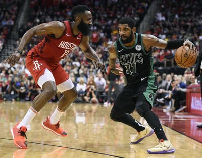 Boston Celtics guard Kyrie Irving, right, dribbles as Houston Rockets guard James Harden defends during the second half in Houston on Thursday. (Eric Christian Smith / AP)