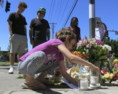 Coco Douglas, 8, leaves a handmade sign and rocks she painted at a memorial in Portland, Ore., on Saturday, May 27, 2017, for two bystanders who were stabbed to death Friday while trying to stop a man who was yelling anti-Muslim slurs and acting aggressively toward two young women. From left are Coco's brother, Desmond Douglas; her father, Christopher Douglas; and her stepmother, Angel Sauls. (Gillian Flaccus / Associated Press)