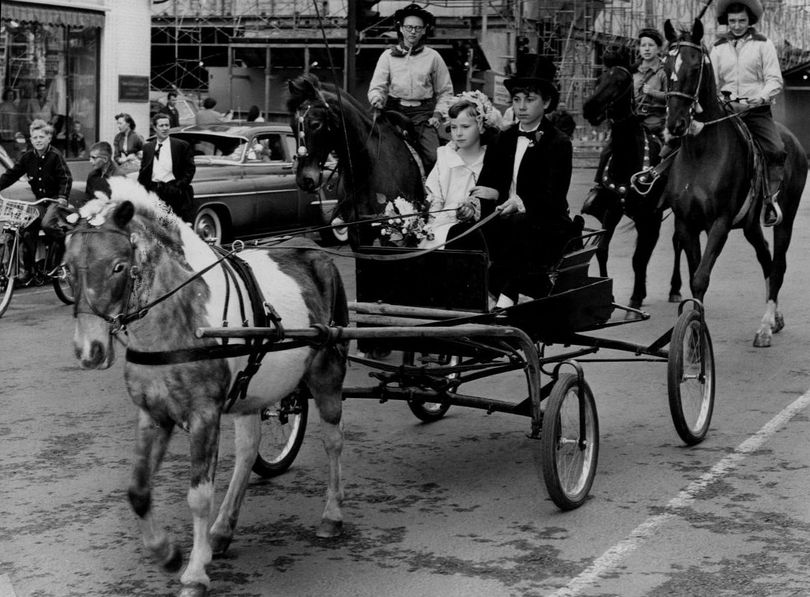 Despite cold weather, nearly 3,500 spectators watched the Junior Lilac Parade on May 14, 1955.  Dressed in old-fashioned costumes and playing newlyweds were Janet Reasoner, 14, as the groom and Christine Childers, 9, as the bride.  (Photo Archive)