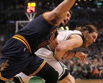 Cavaliers forward Kevin Love, left, is pulled by the arm by Celtics center Kelly Olynyk in Sunday's game. (Thomas Ondrey)