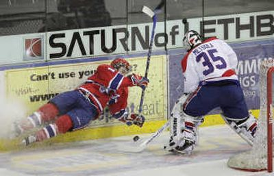 Lethbridge goalie Juha Metsola beats airborne Spokane Chief Justin McCrae to the puck to clear it during Wednesday's 4-1 Spokane win. For   (Photos by David Rossiter For / The Spokesman-Review)