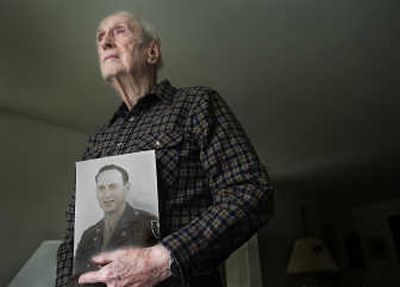 Spokane's John Wills, now 92, was stationed in Iran during World War II to help build 1,000-mile highway and railroad links to the Soviet Union. Millions of tons of U.S. aid was transported through the Persian Corridor to Soviet troops. The photo in his hands shows the young engineer in his military uniform.   (CHRISTOPHER ANDERSON / The Spokesman-Review)