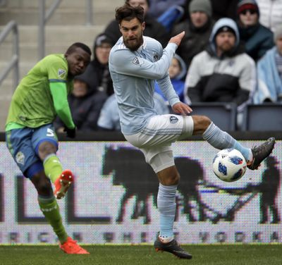 Sporting Kansas City midfielder Graham Zusi, right, blocks a kick by Seattle Sounders defender Nouhou Tolo during the first half. (Orlin Wagner / Associated Press)