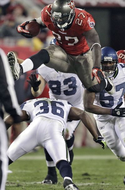 Buccaneers running back LeGarrette Blount hurdles Seahawks safety Lawyer Milloy on a fourth-quarter run. (Associated Press)