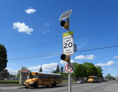 A set of flashing lights and a speed-limit sign warn drivers that this area of North Nevada Street is a 20 mph school zone during certain hours of the day.  (Jesse Tinsley/THE SPOKESMAN-REVI)