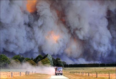 An emergency vehicle races away from a blaze near a structure in the Gippsland region in Australia's Victoria state on Saturday.  Wildfires  killed at least 35 people and razed some 100 homes.  (Associated Press / The Spokesman-Review)