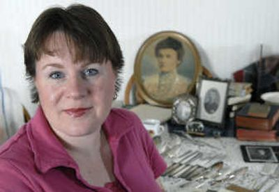 Miriam Midkiff collects her families' memories and artifacts, including a picture of adoptive great-grandmother Nellie Concidine Holst from 1905, shown in background.  (The Spokesman-Review)