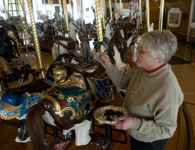 Bette Largent touches up the Looff Carrousel's horse saddles with brown paint Feb. 18. Largent, a professional carousel horse restoration artist, takes care of the historic Looff Carrousel, which is celebrating its 100th birthday this year.  (Colin Mulvany / The Spokesman-Review)