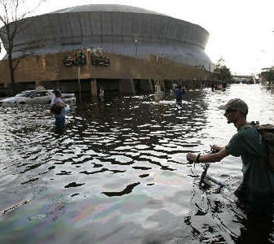 Displaced residents on Wednesday navigate the floodwaters outside the Superdome.  (The Spokesman-Review)