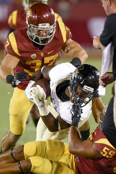 USC linebacker Don Hill, bottom right, pulls down Idaho RB Aaron Duckworth. (Associated Press)