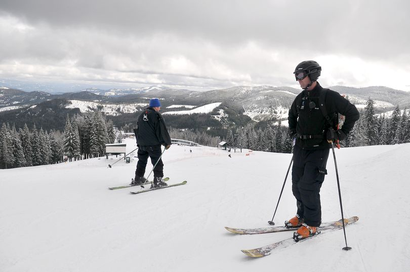 Brad McQuarrie, right, manager of Mt. Spokane Ski and Snowboard Park, watches skiers pass him on the slope just above the main lodge on Friday, March 11, 2011.  The area above the lodge is a bottleneck on busy weekend days, funneling beginners and more advanced skiers into tight quarters, which is one reason the ski area would like to open the Northwest face of the mountain in a proposed expansion. (Jesse Tinsley / The Spokesman-Review)