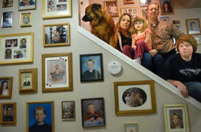 Tricia Ross with her daughter, Bailee, 4, and fiancé Jon Weiland along with her son, Austin, 12, and the family dog Moohna survuived CO poisoning in their split-level Mead home. Now one of several CO detectors hangs with family portraits.   (Brian Plonka / The Spokesman-Review)