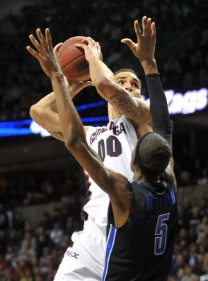 Gonzaga's Robert Sacre looks to shoot over Memphis' Will Barton during Saturday's game at the Arena. (Jesse Tinsley)