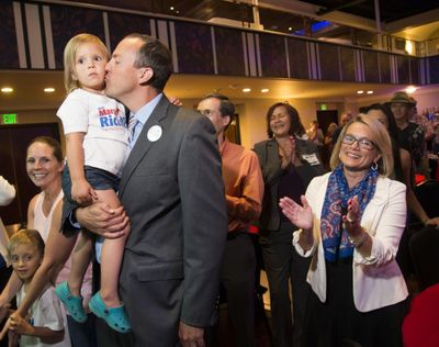 State Rep. Marcus Riccelli, who represents the 3rd Legislative District, kisses his daughter Bryn, 3, and 6th Legislative District candidate Lynnette Vehrs, on right, celebrates early results showing them leading their challengers, Tuesday, Aug. 2, 2016. (Colin Mulvany / The Spokesman-Review)
