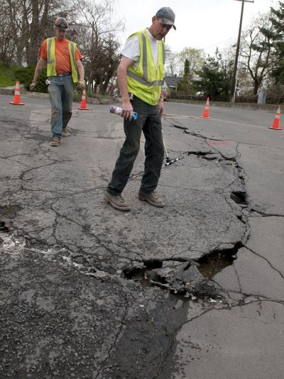 Spokane Water Department workers Brian Strange, in back and Lance Hudkins assess a water main break at Boone Avenue at Summit in West Central.    (Colin Mulvany / The Spokesman-Review)