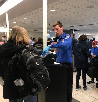 A TSA Officer checks passenger's travel documents at Spokane International Airport. (Emma Epperly / The Spokesman-Review)