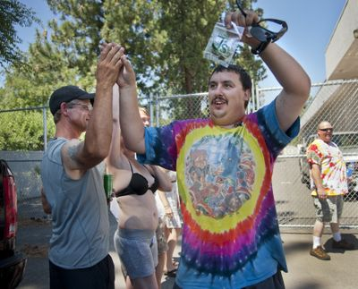 Mike Boyer races through the crowd showing off his 4 grams of pot he bought as the first in line to legally purchase marijuana at Spokane Green Leaf on Country Homes Boulevard.   Hundreds were lined up as sales in Washington began on Tuesday, July 8, 2014. (Dan Pelle / The Spokesman-Review)