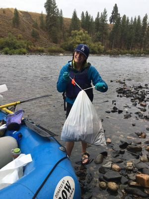 A volunteer works with rafters to collect trash on Sept. 17, 2016, during the annual Spokane River Clean-up and Upriver Scrub. (Spokane River Forum)