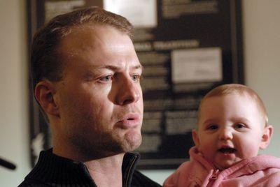 Tim Eyman, holding 8-month-old daughter Riley, talks to reporters in Olympia about his new ballot measure Monday.  (RICHARD ROESLER / The Spokesman-Review)