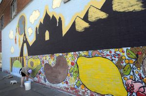 Janice Raschko works on a mural  Thursday as she and her husband, Keith, build the One World Spokane Organic Community Kitchen in the 1800 block of East Sprague.  (Christopher Anderson / The Spokesman-Review)