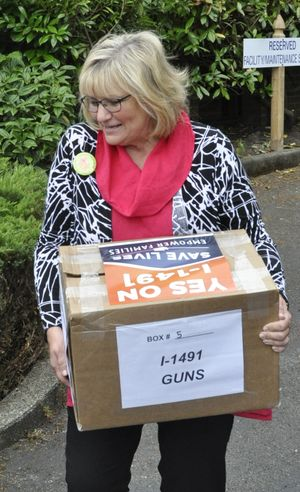 OLYMPIA -- Washington First Lady Trudi Inslee carries a carton of petitions for Initiative 1491, a gun control proposal, to the state elections office on July 7, 2016, as supporters announced they were turning in 330,000 signatures for the measure. (Jim Camden/The Spokesman-Review)