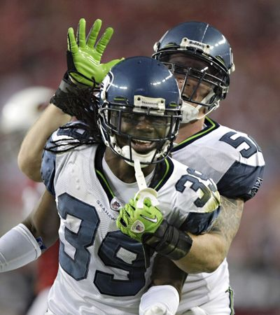 Seahawks Matt McCoy, rear, and Kennard Cox celebrate during Seattle's win over Arizona, which gave the Seahawks a sweep of the NFC West rival Cardinals this season. (Associated Press)