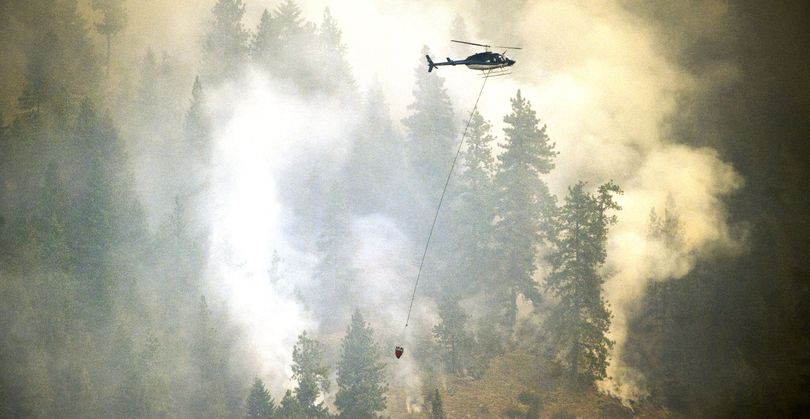A helicopter carries water to douse the Cape Horn fire above Bayview on July 6. (File)