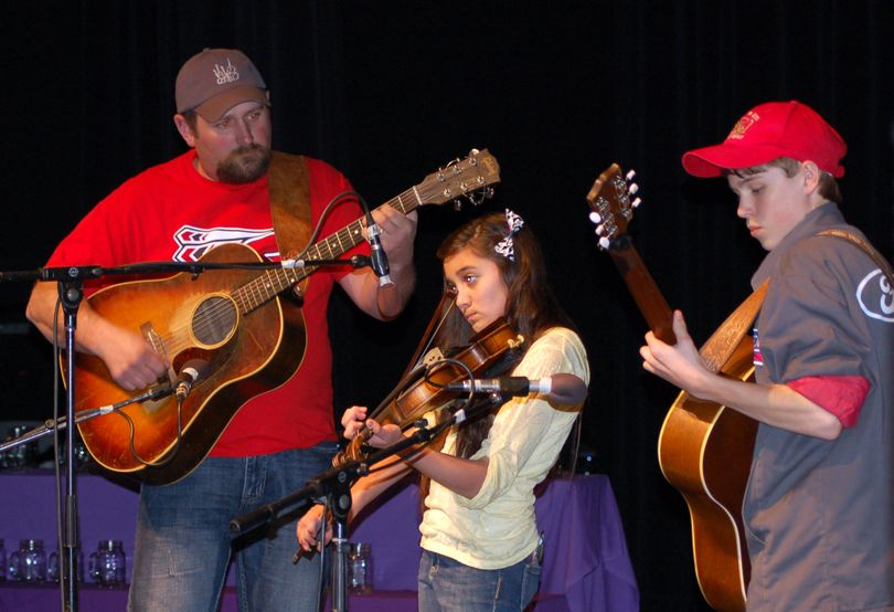 Darrin Meeks, left, and Drew Miller accompany fiddle contestant Dani Jo Meeks during the 2013 Northwest Regional Fiddle Contest.