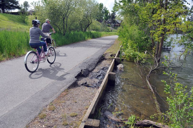 River waters to stay high. Bicyclists ride a stretch of Centennial Trail near Barker Road where the Spokane River laps at the edge of the pavement on Wednesday. The National Weather Service says that rivers around the region will run at high levels through mid-June. (Jesse Tinsley)