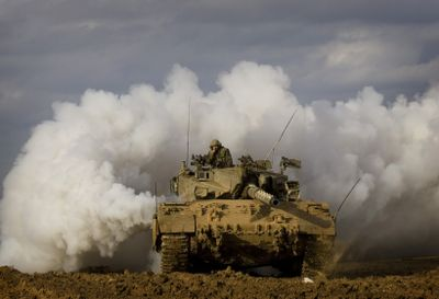 An Israeli tank advances along the Israel-Gaza border Thursday.  More than 750 Palestinians have been reported killed in Gaza since an Israeli offensive began on Dec. 27. At least 11 Israelis have been killed.  (Associated Press / The Spokesman-Review)