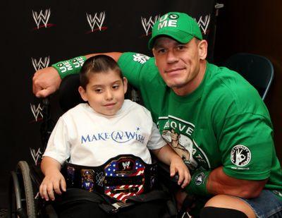 Jonny Littman, poses with WWE superstar John Cena in Uniondale, N.Y. (Associated Press)
