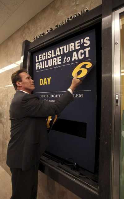 """After the Legislature's approval of a state budget, Gov. Arnold Schwarzenegger removes the numbers from the """"deficit clock"""" he employed to keep track of the duration of a special session called to address Calfornia's fiscal problems.  (Associated Press / The Spokesman-Review)"""