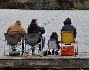 A family focuses on catching fish in Williams Lake from the dock at Bunker's Resort. They were fishing on April 28, 2013, the opening day of Washington's lowland trout fishing season.  (Rich Landers)
