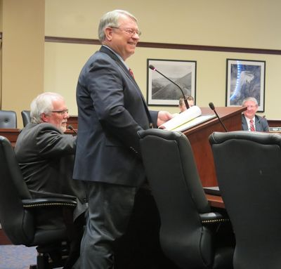 Idaho Secretary of State Lawerence Denney grins as he responds to questions from members of the House State Affairs Committee on Tuesday, Feb. 13, 2018, about campaign finance reform legislation proposed unanimously by an interim legislative committee. At left is Chief Deputy Secretary of State Tim Hurst; at right is Rep. Lynn Luker, R-Boise. (Betsy Z. Russell / SR)