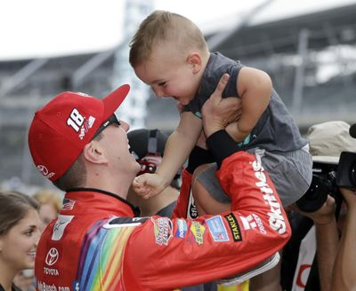 Kyle Busch talks with his son, Brexton, after winning the pole for the NASCAR Cup auto race at Indianapolis Motor Speedway, in Indianapolis on Saturday, July 22, 2017. (Darron Cummings / Associated Press)