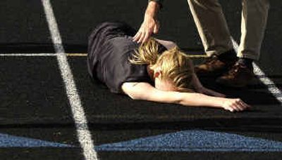 North Central's Stephanie Krebs collapses at the finish line after winning the 400-meter run in the Greater Spokane League championship quad meet.North Central's Stephanie Krebs collapses at the finish line after winning the 400-meter run in the Greater Spokane League championship quad meet.  (Brian Plonka/Brian Plonka/ / The Spokesman-Review)
