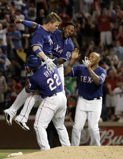 Texas Rangers players celebrate with Hank Blalock, top left, after his winning hit.  (Associated Press / The Spokesman-Review)