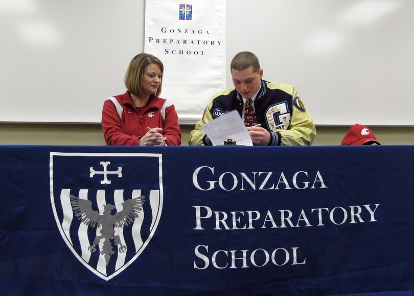 With his mother Kathleen Cronquist by his side, Gonzaga Prep High School football player Travis Long signs his National Letter of Intent Wednesday to play football at WSU in 2009. COLIN MULVANY The Spokesman-Review (Colin Mulvany / The Spokesman-Review)