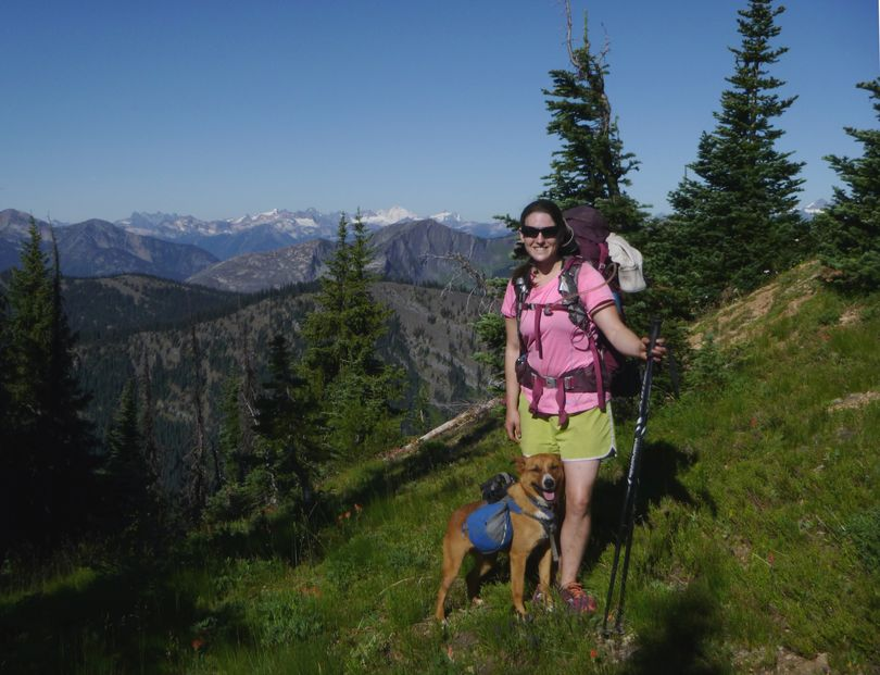 Samantha Journot pauses with her dog, Duke, on the Pacific Crest Trail -- Mount Baker's white summit showing in the background -- during a 100-mile backpacking trek through the Pasayten Wilderness. (Rich Landers)