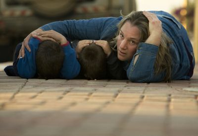 An Israeli woman  covers the heads of her children Wednesday during  an alarm warning of incoming rockets  in Kfar Azza, southern Israel, near the border with Gaza.  (Associated Press / The Spokesman-Review)