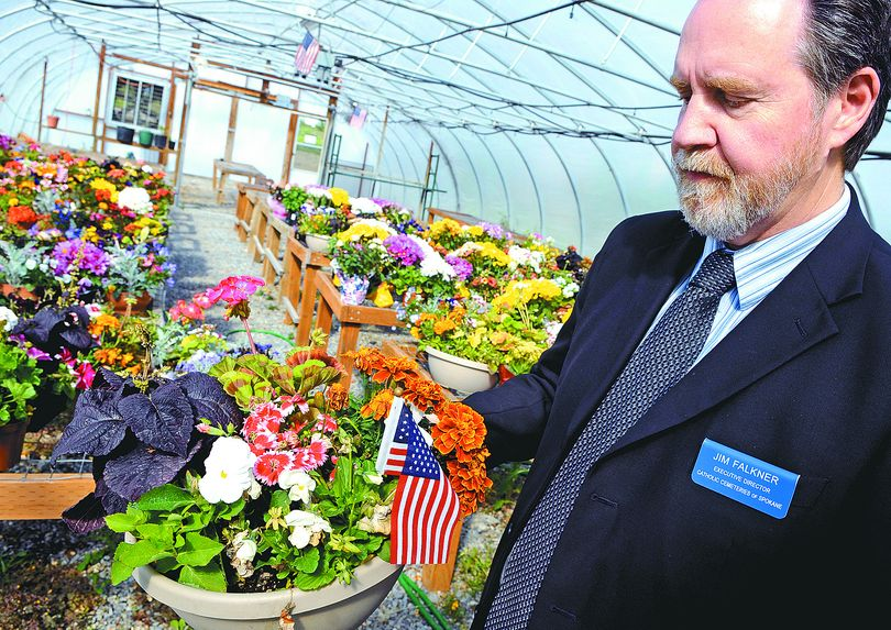 Jim Falkner, executive director of Catholic Cemeteries of Spokane, holds  one of the 61 Memorial Day planters that were recovered among those stolen over the past 10 days. The flowers are now on the shelves in the greenhouse at Holy Cross Cemetery.  (Dan Pelle)