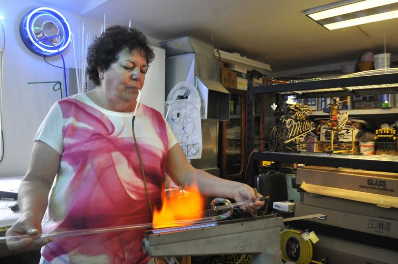 Dana Eberly, of Spokane Valley, heats a glass tube with a special torch setup before bending it. She said plastic signs took over in the 1970s, but neon came back in the 1980s. Now LED lights are popular. (Jesse Tinsley)