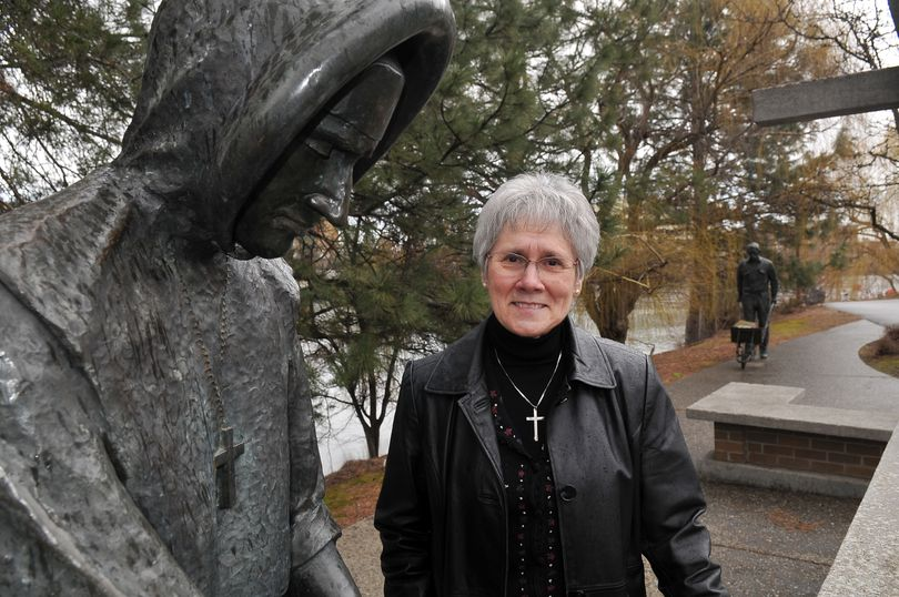Sister Rosalie Locati, director of mission and values for Providence Sacred Heart and Providence Holy Family hospitals, stands beside Ken Spiering's sculpture in Riverfront Park. It commemorates the arrival of the Sisters of Providence, who built Sacred Heart on the banks of the Spokane River in 1886. Locati is the only Sister of Providence still working full time at Sacred Heart Medical Center. (Jesse Tinsley)