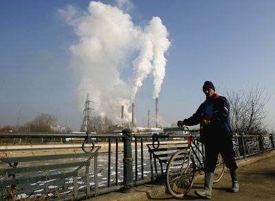 A man pushes his bike Wednesday past one of the main heating plants in Bucharest, Romania.  A pipeline bringing Russian gas to Romania through Ukraine was turned off Wednesday morning.  (Associated Press / The Spokesman-Review)
