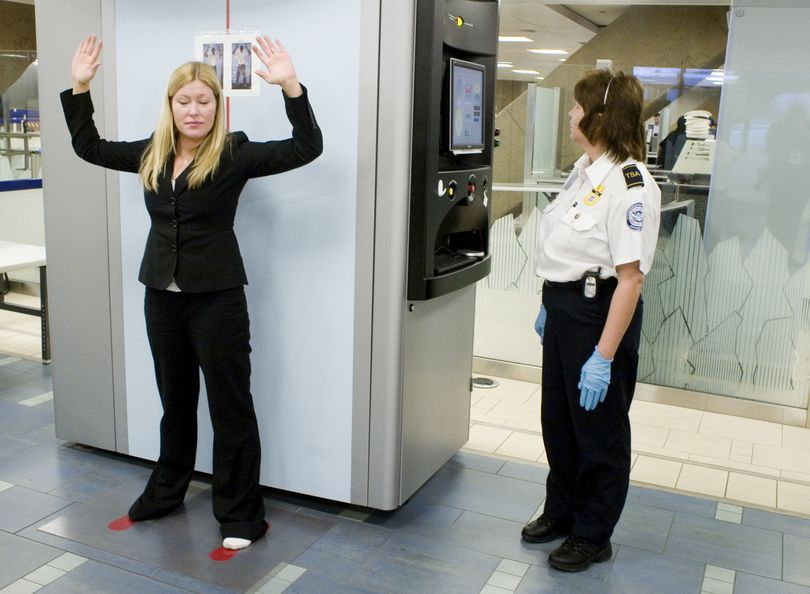 A Transportation Security Administration (TXA) agent, right, scans airline passenger Kelsi Dunbar, using the new