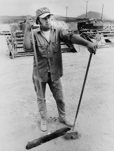 Phil Gage, an employee of Best Way Equipment in Palouse, Washington, takes a break from sweeping off ash-covered farm implements in this photo from June 10, 1980. (Phil Schofield / S-R)