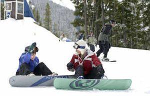Stefani Enfield, 18, of Post Falls, helps her 12-year-old brother, Austin Enfield, left, with his snowboard for much-appreciated late-season skiing at Silver Mountain on Saturday.   (Tom Davenport/ / The Spokesman-Review)