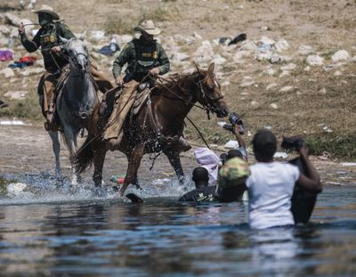 U.S. Customs and Border Protection mounted officers attempt to contain migrants as they cross the Rio Grande from Ciudad Acuña, Mexico, into Del Rio, Texas, Sunday, Sept. 19, 2021. Thousands of Haitian migrants have been arriving to Del Rio, Texas, as authorities attempt to close the border to stop the flow of migrants.  (Felix Marquez)