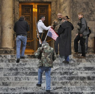 OLYMPIA – Second Amendment rights protestors openly carrying their firearms gathered outside the legislative chambers in the Capitol during a January 2015 protest. Openly carried guns in the galleries were banned shortly after that demonstration. (Jim Camden / The Spokesman-Review)